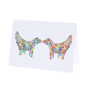 Greeting card showing two Super Lambanana statues kissing each other, in Tula Moon's distinctive colourful patchwork style.