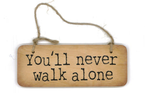 Wooden hanging sign with the phrase 'you'll never walk alone'