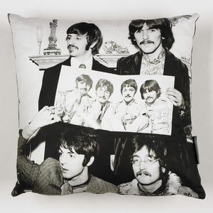 Square cushion printed with a picture of the beatles holding up a promotional photo of themselves