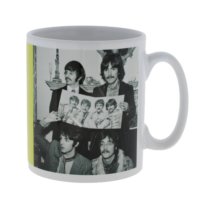White mug, wrapped with a black and white photo of the beatles holding a promotional photo of themselves