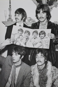 Portrait oriented print of a black and white photograph of the beatles, holding up a promotional photo of themselves