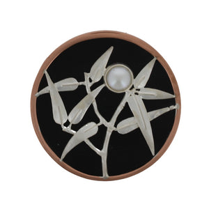 Japanese inspired brooch, a silver sprig of bamboo, set with a pearl on a circle of black resin with a copper surround