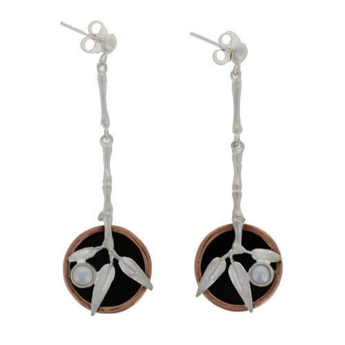 Pair of silver earrings, pearl studs with hanging pendants. The chain connecting them designed to look like a bamboo stalk and the pendants like the foliage, also set with a pearl and on a circle of black resin with a copper surround.