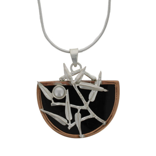 Pendant hanging on a silver chain. The pendant is a semi-circle, silver bamboo foliage set with a bamboo on a black resin backing surrounded by copper.