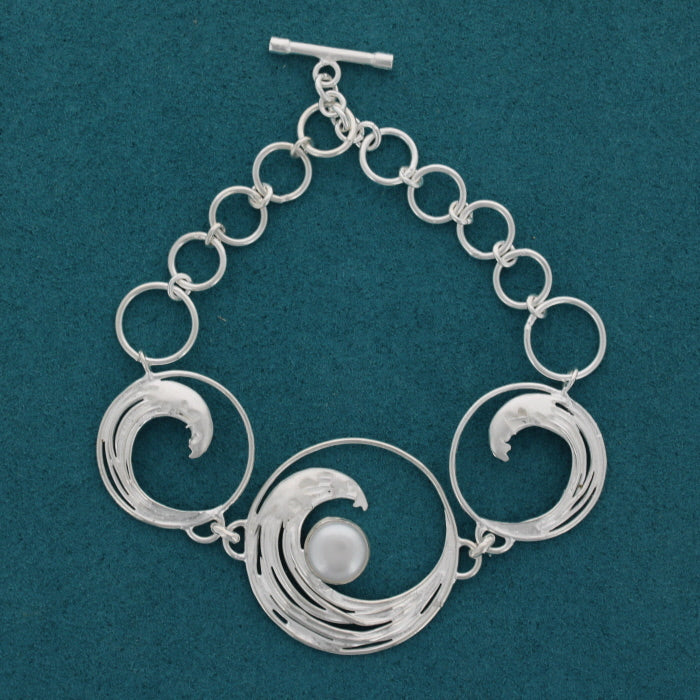 Bracelet on a blue background. In silver with three pendant showing an outline from the iconic great wave painting, the largest in the centre is set with a pearl