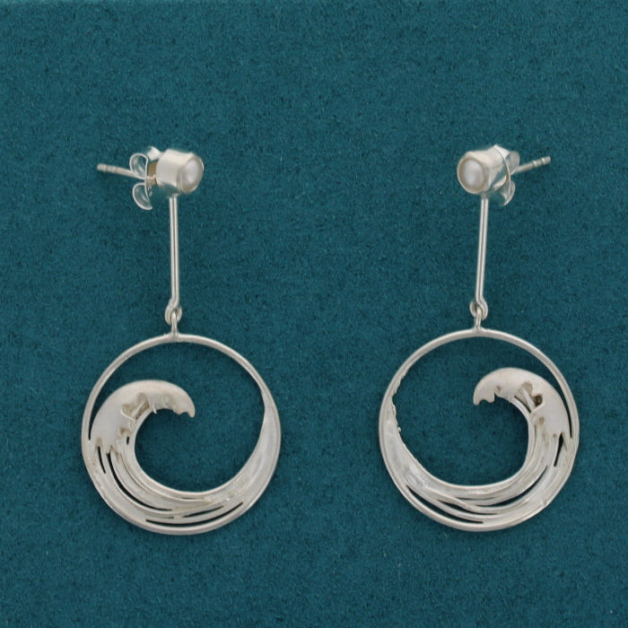 Pair of silver earrings with a pearl stud and hanging silhouettes, showing mirrored versions of the great wave, from the iconic japanese painting.