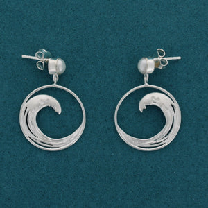 Pair of silver earrings on a blue background. A pearl stud with an outline of the great wave (from the iconic japanese painting of the same name) handing in a circle below