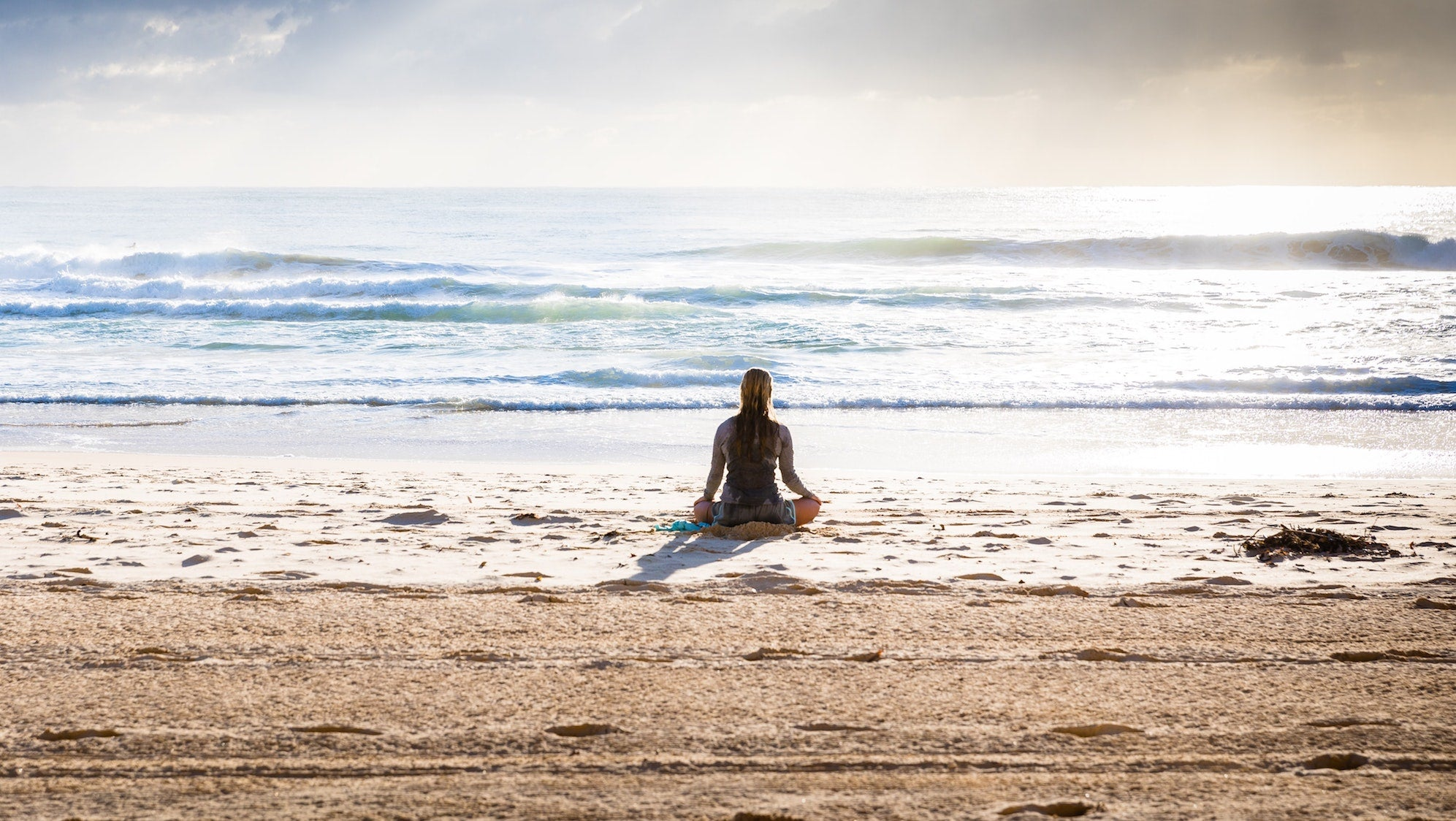 Girl meditating on the beach