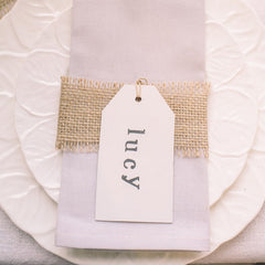 cream luggage tags stamped with names for wedding place settings