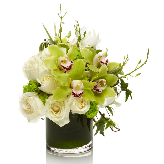 A fresh mix of white roses and lime cymbidium orchids with grass and accents of greenery in a glass vase.