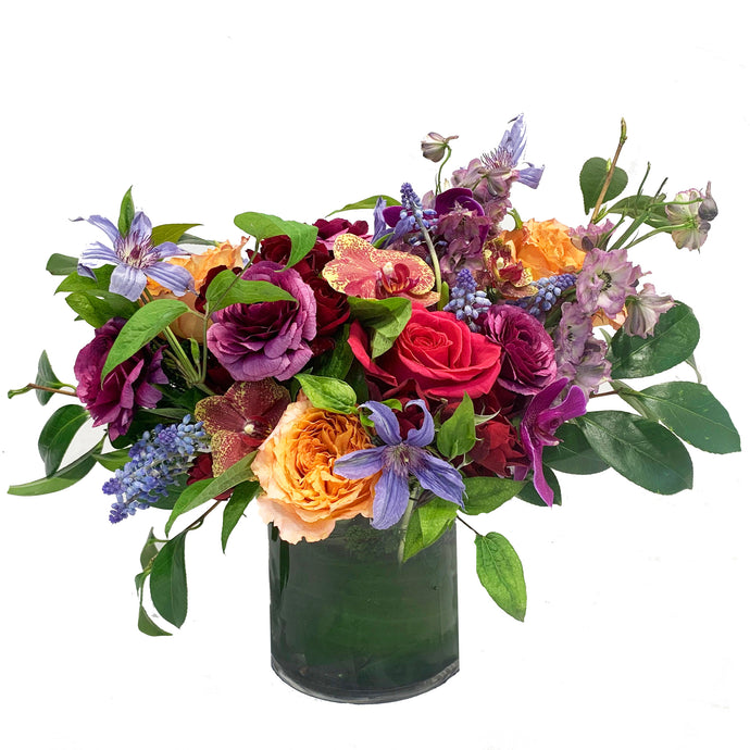 A whimsical vibrant garden-style arrangement using bright colored premium blooms accented with seasonal greenery in a chic glass vase.