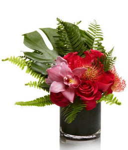 An exotic blend of pink roses, orchids, and other tropical seasonal flowers with modern greenery.
