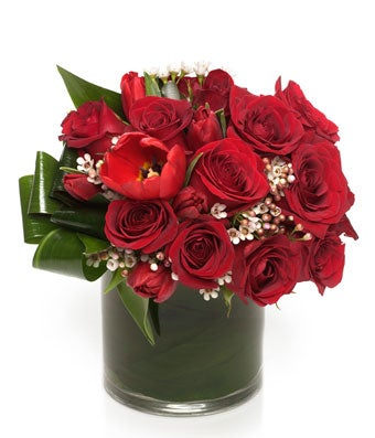 A delicately designed low and lush arrangement of premium red flowers accented with greenery.