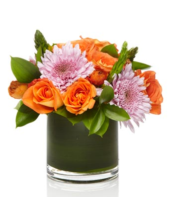 A mixed flower arrangement of lavender mums and orange roses arranged with greens in a glass vase.
