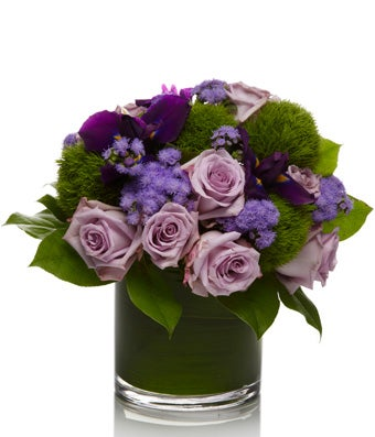 A classic arrangement of purple roses arranged with elegant greens and seasonal fillers.