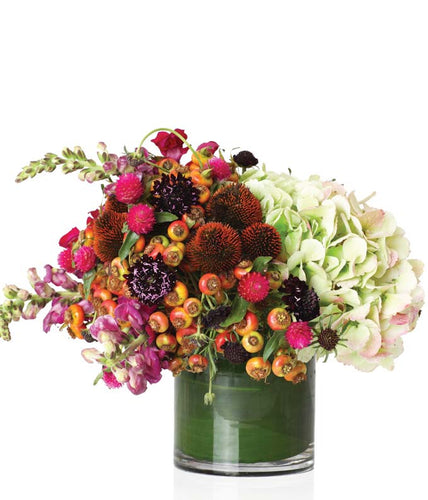 A mix of blooms such as hydrangea, stock, scabiosa, berries, and celosia arranged in a glass vase.
