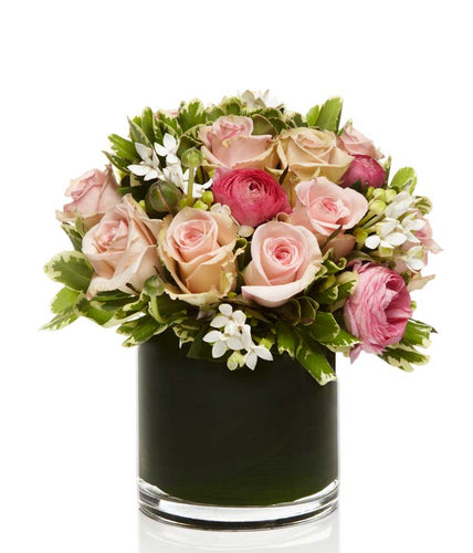 A beautiful mix of premium pink roses artfully arranged in a chic glass vase.