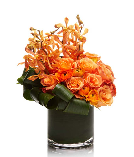 Luxury Arrangement of Orange Roses, Ranunculus, and Mokara Orchids.
