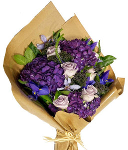 An elegantly wrapped bundle tied neatly together with fresh luxury purple and lavender blooms