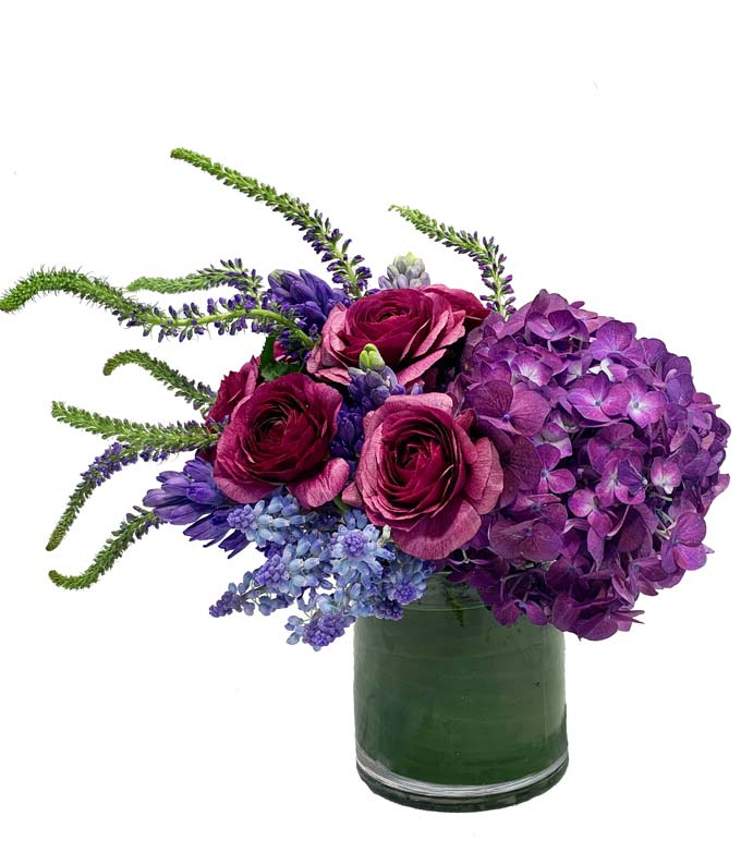 A unique grouped arrangement with radiant purple and lavender blooms.