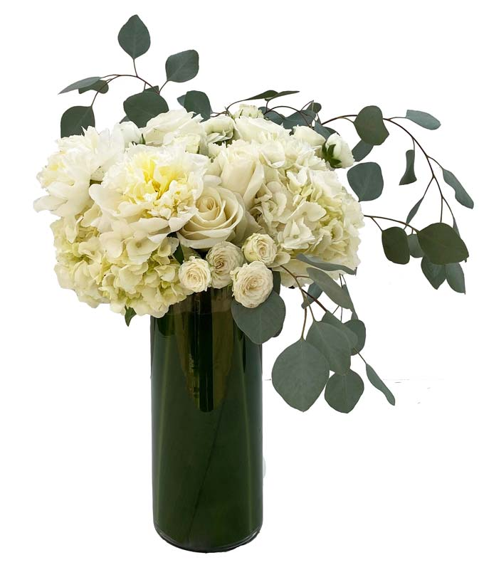 A tall and elegant arrangement of all-white blooms such as roses and hydrangea accented with eucalyptus.