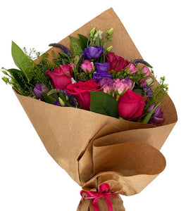 Soft blooms in various hues of red, pink, and purple wrapped in brown kraft paper
