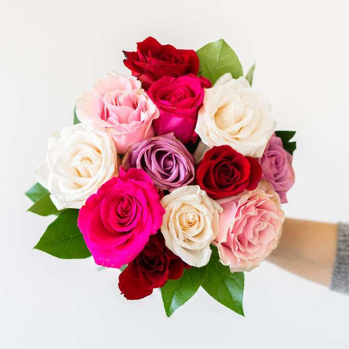 Bouquet of 12 stems of brightly colored roses such as pink, purple and white.