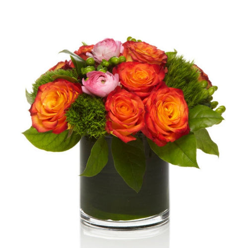A bright arrangement of orange roses and premium pink seasonal blooms with modern greenery arranged in a chic glass vase.