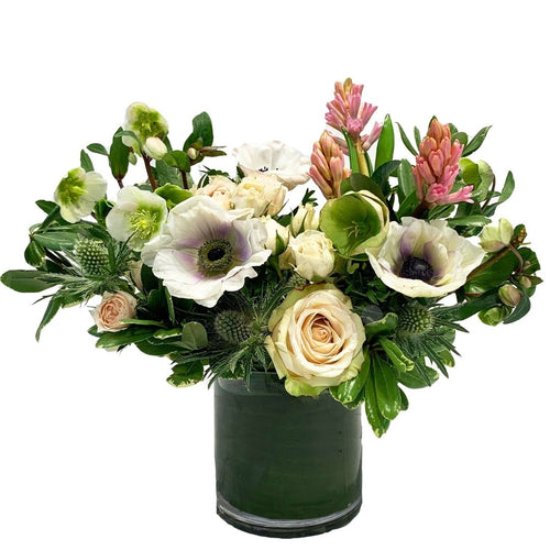 A lush garden-style arrangement elegantly designed with pink & cream colored premium blooms with modern greenery
