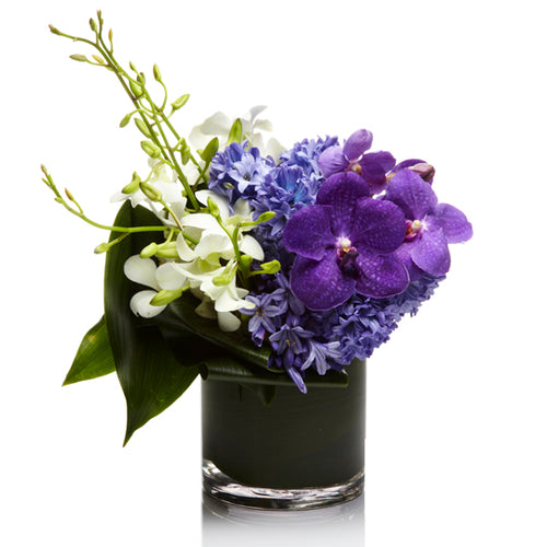 A luxe arrangement of purple and white orchids and hyacinth, arranged in a glass vase with modern greenery.