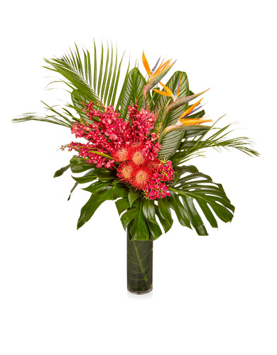 An arrangement of tropical varietals in vibrant reds and oranges designed in a chic glass hurricane vase
