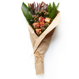 A rustic bundle of warm red blooms such as roses and berries accented with greenery with a gift message.