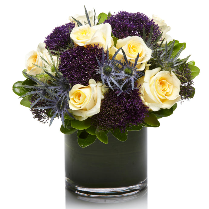 A Elegant Arrangement of Blue Thistle, Cream Roses and Purple Fillers - H.Bloom
