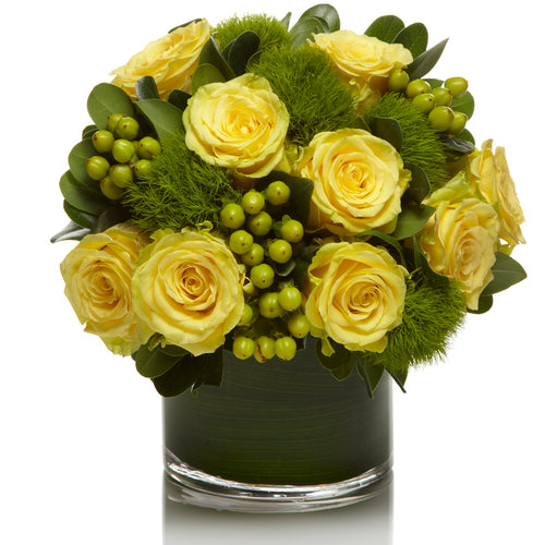 A modern mix of sunny yellow roses, green dianthus, and lime berries accented with greens in a chic glass vase.