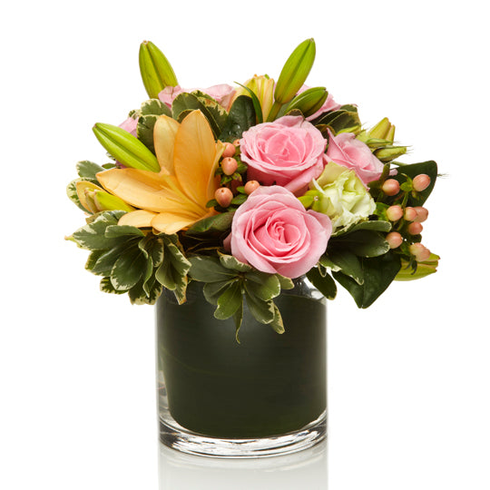 An arrangement of soft pink roses, orange lilies, and peach berries with a touch of greens
