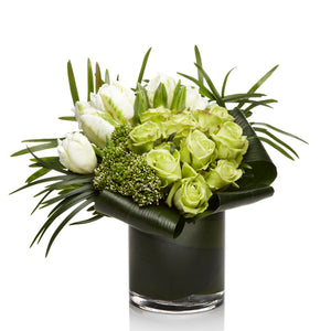 A luxe arrangement of soft green roses, white exotic blooms, and greens in a glass vase.