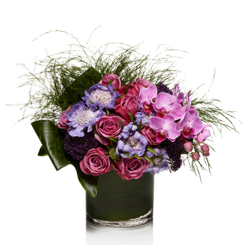 A Garden -Style Arrangement of Lavender, Purple and Pink Seasonal Blooms with Exotic Greenery - H.Bloom