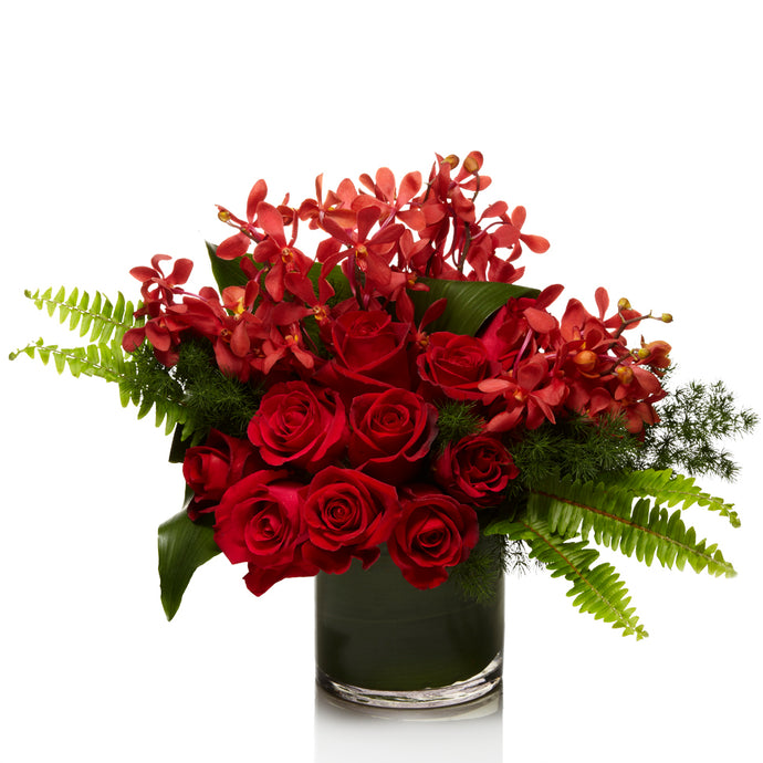 A lush arrangement of red roses and red orchid varieties, accented with modern greens in a premium glass vase.