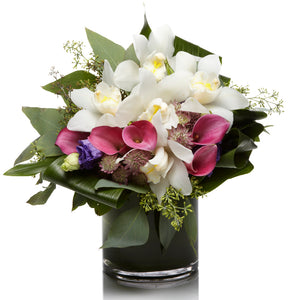 A beautiful mix of white orchids, pink calla lilies, and purple lisianthus accented with eucalyptus in a premium glass vase.
