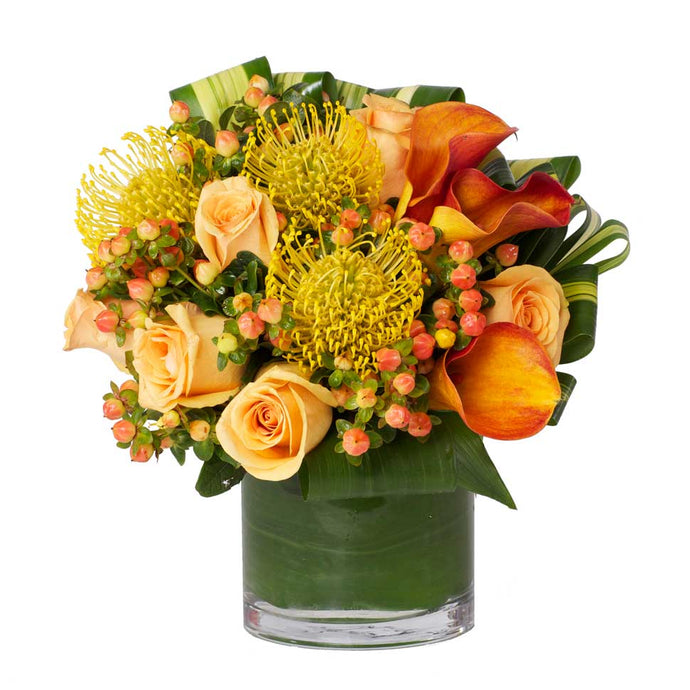 A vibrant mix of bright orange and yellow blooms such as roses, protea, and calla lilies accented with berries and modern greens.