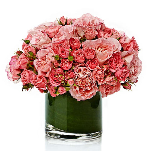 A chic mixed arrangement of assorted pink rose varieties arranged neatly in a premium glass vase.