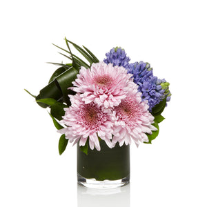 A cute mix of lavender mums and purple spring flowers arranged with modern greens.