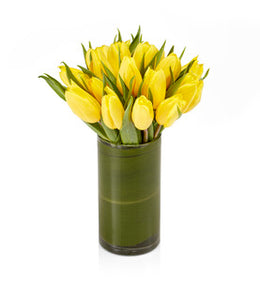 A classic arrangement showcasing yellow tulips in a glass hurricane vase.
