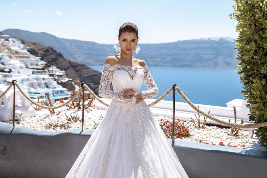 Luxurious wedding dress with fluffy skirt-train. Figured open shoulders add elegance to the look. The bottom of the skirt is decorated with hands embroidery, which only emphasizes the luxury of the look.