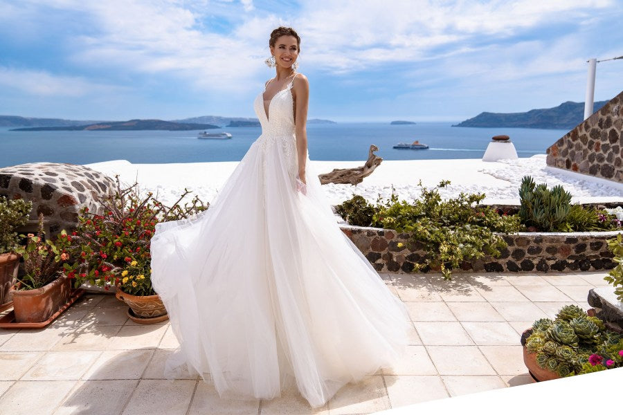 Airy wedding dress on a straps with a fluffy skirt-train. The bodice of the dress skillfully decorated with guipure, embroidered with beads, pearls and sequins. The dress is decorated with low-cut in front, creating special contrast between delicate top and fluffy bottom.