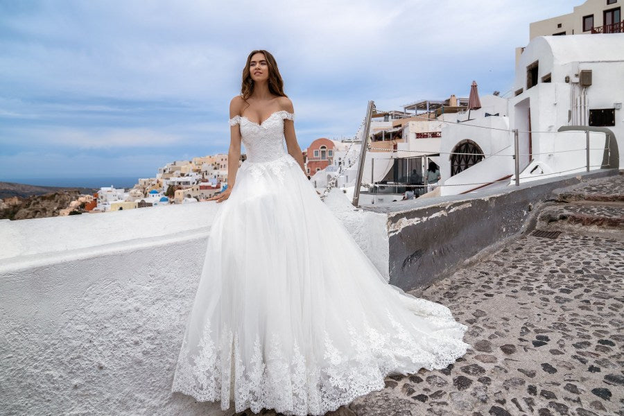 Luxurious wedding dress with open shoulders and puffy skirt-train. The bodice of the dress is decorated with hands embroidery with sequins, crystals and flowers. The skirt made of shining fabric, also is decorated at the bottom, which adds fabulousness to the look.  You have chosen the model with a veil. We recommend to this dress the veil F-060.