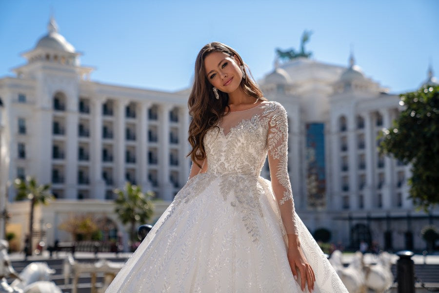 Luxurious long-sleeved wedding dress with a fluffy guipure train skirt. The back is fastened with buttons. The pleated skirt is made of guipure embroidered with sequins