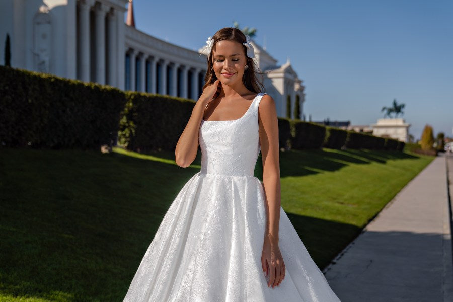 """Fabulous wedding dress with a bodice on the straps and a pleated skirt. Corset with a modern """"square"""" neckline. The model is made of chantelle fabric with sequin and """"mikado"""". The back is also decorated with a neckline, it is fastened with buttons."""