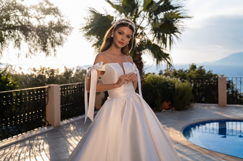 Royal wedding dress with a fluffy skirt with a train and off shoulders. The model is made of shiny mikado fabric. Open shoulders adorn flirty bow ties. The waist is also emphasized by a removable belt with a bow in front and behind, leaving the bride with a choice.