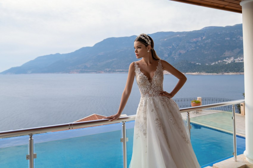 A light wedding dress on the straps with a soft skirt with a train. A seductive translucent bodice to the waist is decorated with a deep neckline in front. A graceful back is emphasized by a V-neck. The model is decorated with guipure, embroidered with silver beads and sequin.